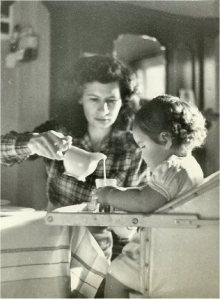 1951  Mom pouring me milk while we're having our tea.