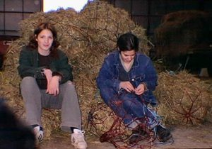 Our daughters, sitting on the haynets they'd stuffed, at the SHAPE riding club when it was at Bauffe, Belgium. 1st generation digital photo