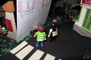 "My main character (the brown haired character at the back) and her colleagues are surprised to find the missing man outside their office, lying in a stairwell near the road (the white stripes are a pedestrian crossing). The back wall of the ""office"" is open (it's a child's play set), so I had to put in a paper wall to ever so slightly increase the realism."